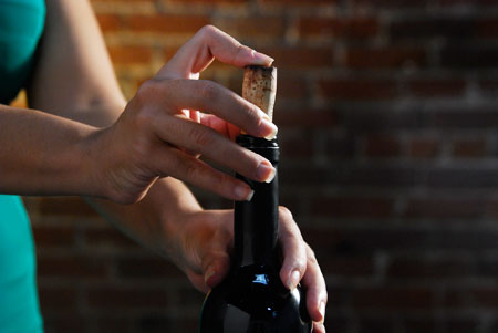 Putting the cork back into an open bottle for later enjoyment. (Photo by Danny Diamond.)