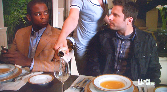 White wine being poured for Shawn (James Roday) while Gus (Dulé Hill) pretends he's important enough to text.